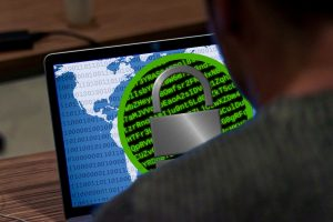 man using laptop with encrypted information on screen