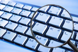 computer keyboard with magnifying glass hovering over