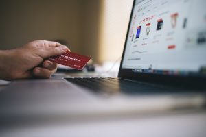 person holding credit card while viewing ecommerce site