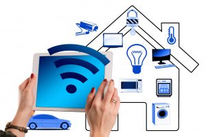 illustration of smart home surrounded by objects, devices, a car, and a person holdling a tablet with a Wi-Fi symbol projecting outwards from the screen